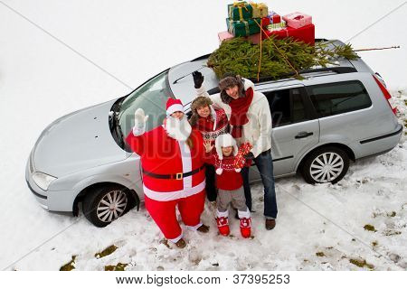 Waiting for Christmas, Santa Claus - family is carrying Christmas tree and gifts on the roof of the car