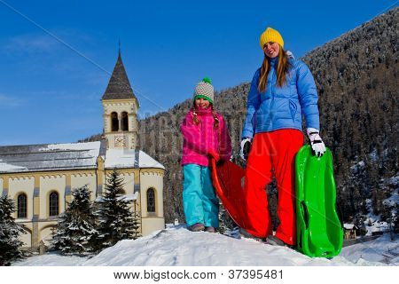 Winter, snow and fun - girls sledding at winter time