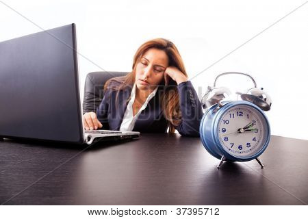 Tired young business woman sleeping next to his laptop computer at the desk, isolated on white