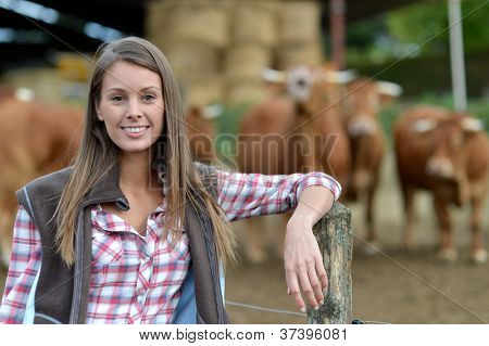 Smiling farmer woman standing by cattle outside