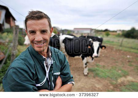 Criador de vaca sorridente de pé na frente do rebanho de vacas