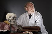 stock photo of jekyll  - Evil doctor with surgical tools and bloody corpse - JPG