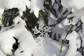 Fir branches in the snowdrift with Christmas snowflake