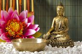 stock photo of buddha  - asian bronze buddha sculpture sitting in meditation behind a singing bowl - JPG