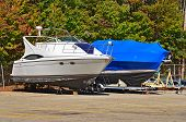 image of tarp  - Pair of power boats in outdoor storage area - JPG