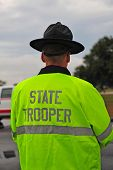 stock photo of trooper  - State trooper wearing yellow raincoat taken from behind - JPG