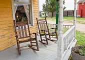 picture of lace-curtain  - Two hardwood rocking chairs on the white washed porch of an old western house with yellow pealing paint and lace curtain framed window - JPG