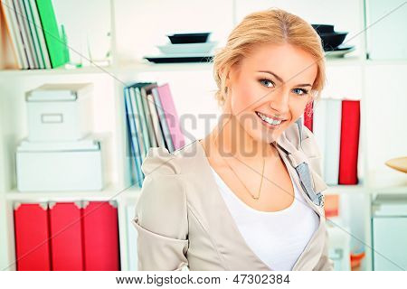 Portrait of a pretty smiling blonde woman at office.