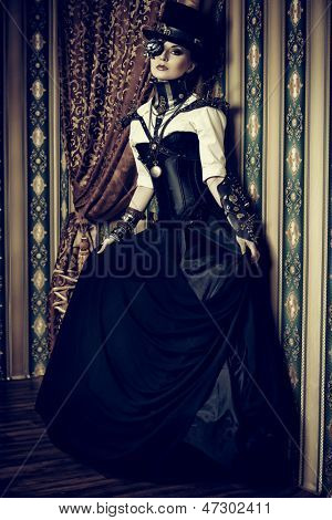 Full length portrait of a beautiful steampunk woman over vintage background.