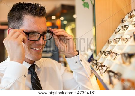 Customer In Optometrist's Shop Choosing The Right Frame