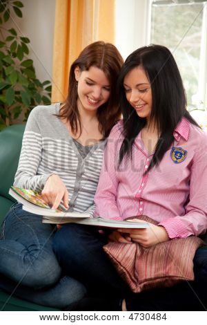 Two Young Women While Shopping In The Catalog
