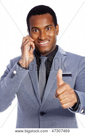 Happy smiling young business man talking on the phone and gesturing thumbs up