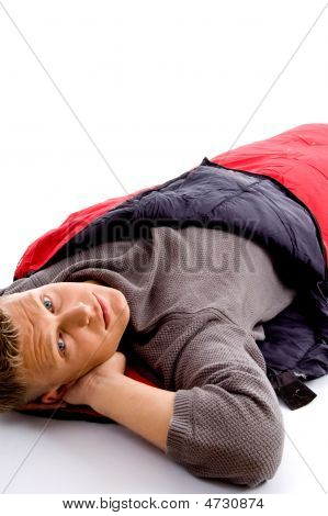 Attractive Man Posing With Red Sleeping Bag And Looking At Camer