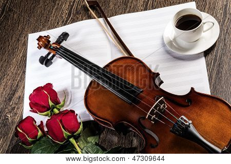 Violin, rose, coffee and music books