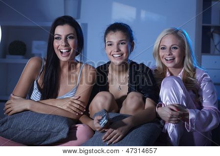 Happy roommates watching tv at home at night, wearing pyjamas, smiling happy.