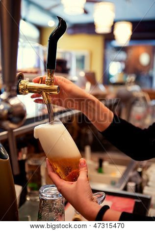 Detail of a hand filling pint of beer in bar