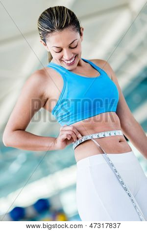 Gym woman taking measurements with a tape measure