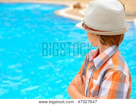 Summer portrait of carefree little boy in hat outdoor near swimming-pool