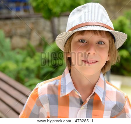 Summer portrait of cheerful carefree little boy in hat outdoor