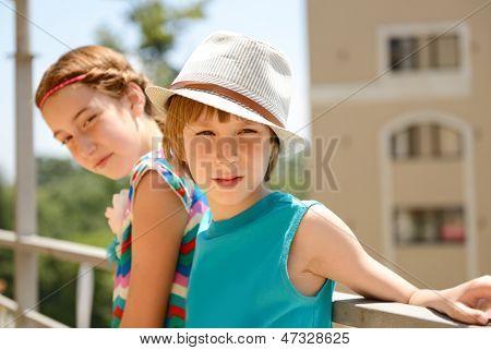 little boy in hat with attractive girl, summer outdoor portrait