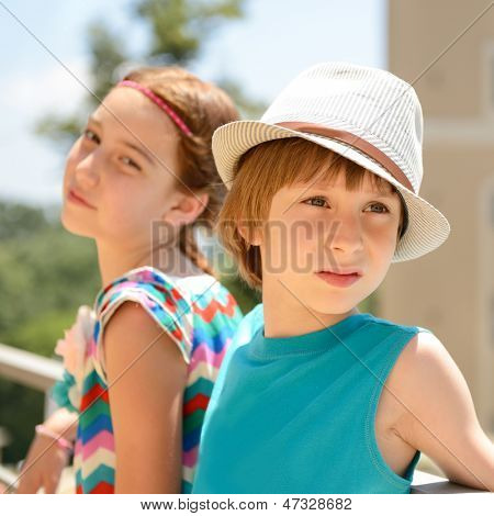 little boy in hat with attractive girl, summer outdoor portrait