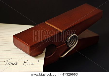 Low key still life of wooden oversized clothespin with handwritten reminder to 'Think Big'.  Macro with shallow dof.