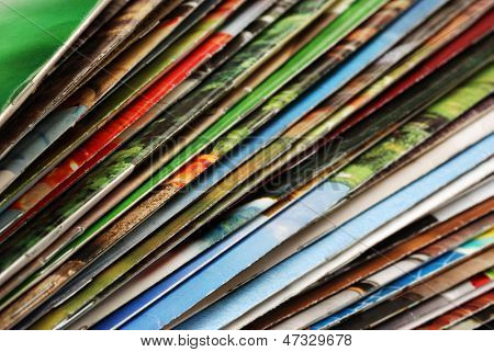 Colorful abstract background image of stacked magazines with slightly worn edges. Macro with extremely shallow dof.