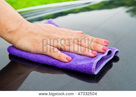 A Hand Drying A Back Car With A Synthetic  Cloth