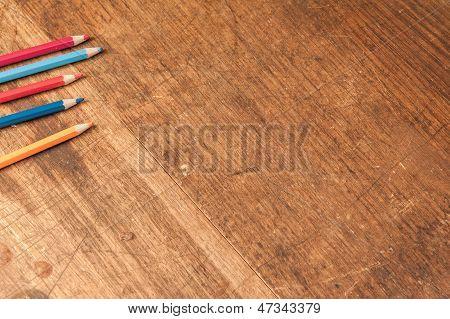 Tapa de tabla de madera con lápices de colores