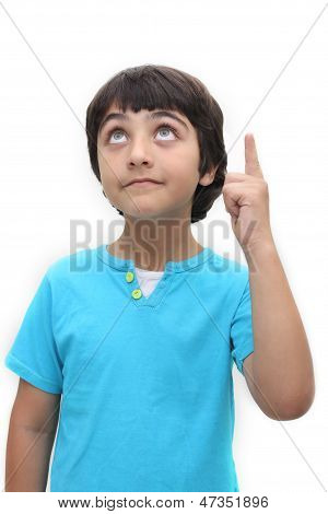 An eight year old boy looking up and pointing with one finger