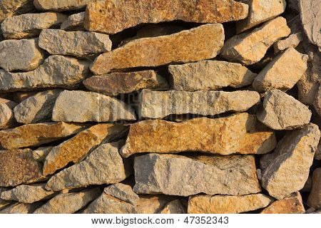 Wall Made Of Natural Stone In The Evening Sun
