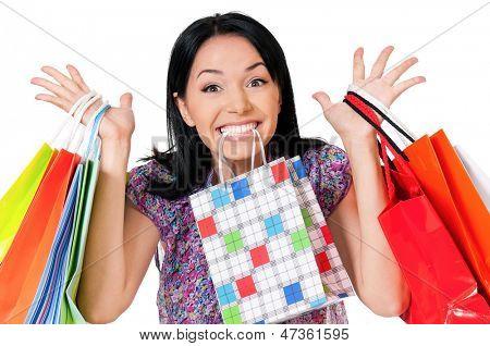 Shopaholic shopping woman holding many shopping bags, isolated over white background
