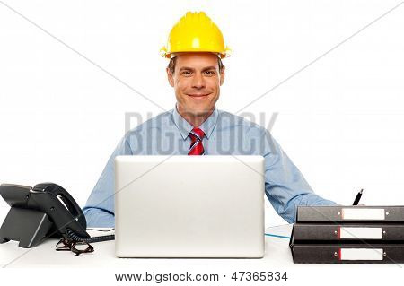 Architect Wearing Safety Hat And Using Laptop