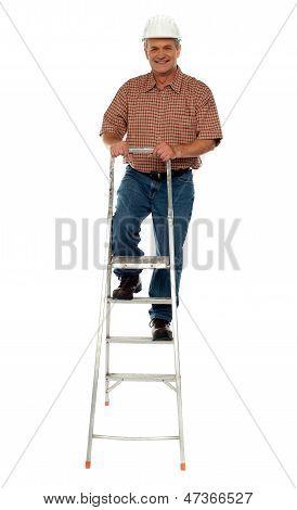 Worker Wearing Hard Hat Climbing Ladder