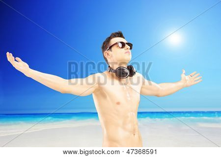 Male tourist with speakerphones spreading his arms and gesturing freedom, next to a sea on a sunny day