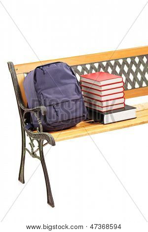 Studio shot of a wooden bench with books and school bag on it, isolated on white background