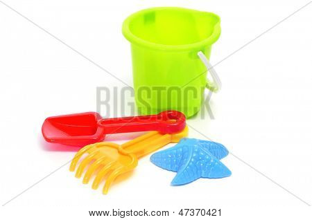 closeup of a sand / beach toy set with a pail, shovel, rake and star-shaped mold of different colors on a white background