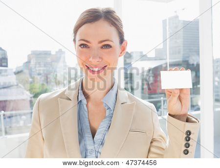 Smiling businesswoman showing blank business card in bright office