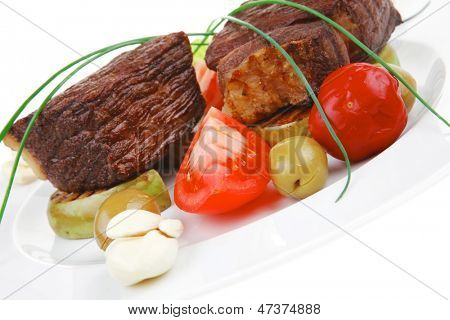 savory food : roast beef garnished with baked apples , green and black olives on white plate isolated over white background