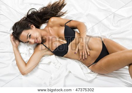Beautiful and sexy woman with a black lingerie lying on bed, isolated on white background