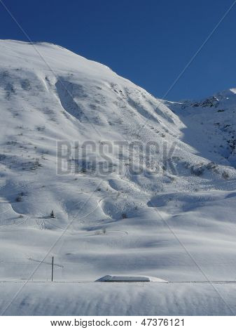 Ski lines run down a well traversed slope Andermat, Switzerland