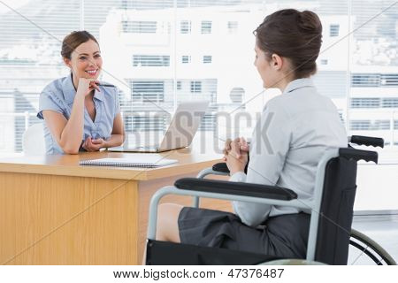 Businesswoman listening to disabled job candidate in her office and smiling