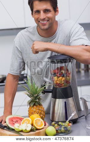 Attractive man leaning on his blender with several fruits inside