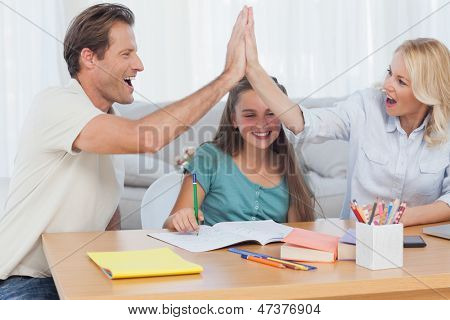 happy parents high fiving in front of their daughter