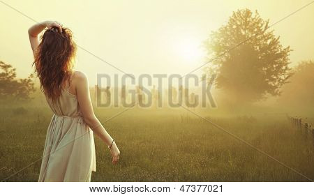 Cute lady walking through the meadow