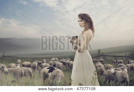 Young pretty cheerful woman with lamb on a countryside