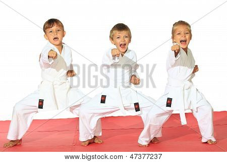 Three children in kimono hit a punch on a white background