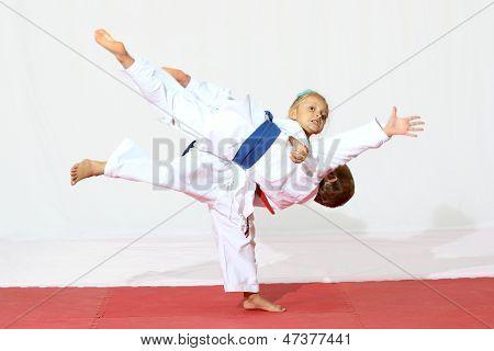 A girl throws a boy in a kimono sports throw
