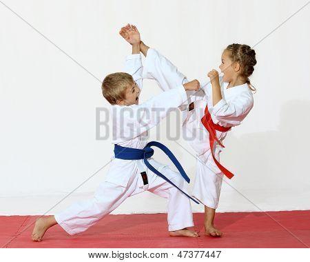 Mädchen in einem Kimono-Treffer-Fuß-Jungen in einen Kimono trifft eine hand