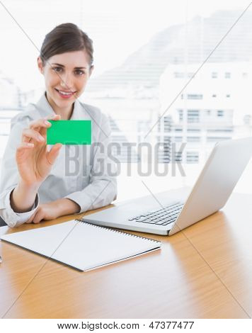 Pretty businesswoman showing green business card at her desk in office